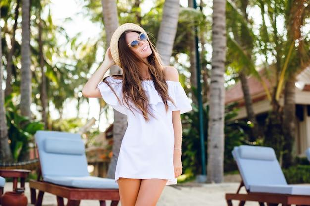 Jolie fille en lunettes de soleil marron et chapeau de paille sourit largement et tient son chapeau avec une main