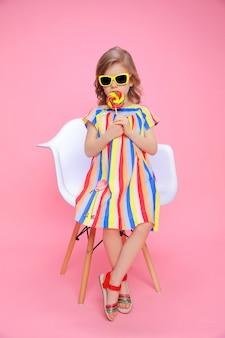 Jolie fille à lunettes de soleil avec sucette