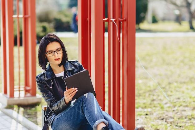 Jolie fille à lunettes avec tablette au parc
