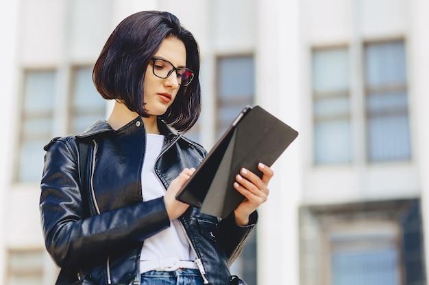 Jolie fille à lunettes avec tablette à l'extérieur