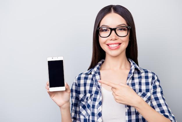 Jolie fille à lunettes et vêtements décontractés indique sur mobile