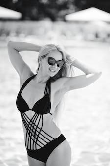 Jolie fille en maillot de bain noir et lunettes de soleil sur fond de piscine