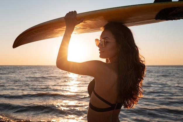 Jolie fille en maillot de bain noir tient une planche de surf au-dessus de sa tête sur la plage de sable près de la mer au coucher du soleil.