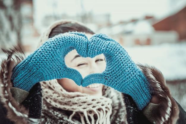 Jolie fille avec des mains en forme de coeur dans les gants