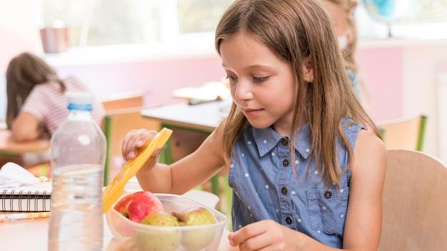 Jolie fille mangeant au concept de l'école