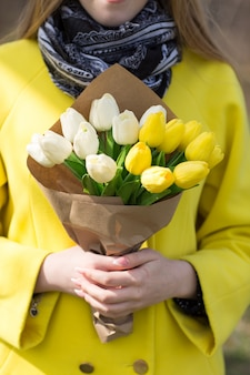 Jolie fille en manteau jaune avec des fleurs blanches et jaunes