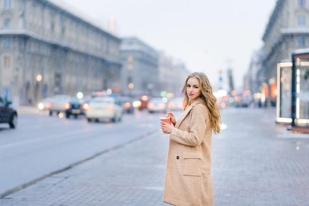 Une jolie fille en manteau se tient dans la rue et tient un gobelet en papier rouge et blanc
