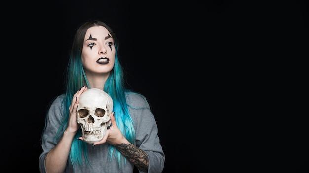 Jolie fille avec le maquillage arlequin tenant le crâne