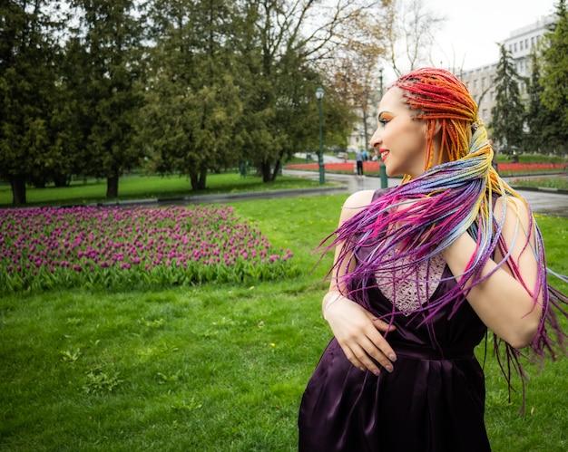 Jolie fille avec un maquillage pailleté coloré et de longues fausses tresses multicolores dans une robe violette en satin. sourire et se serrer dans ses bras et tresses lumineuses lors d'une promenade dans un parc printanier en fleurs.