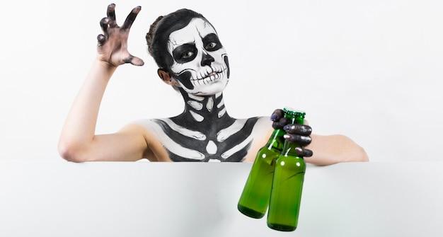 Jolie fille avec maquillage squelette tenir une bouteille en verre verte