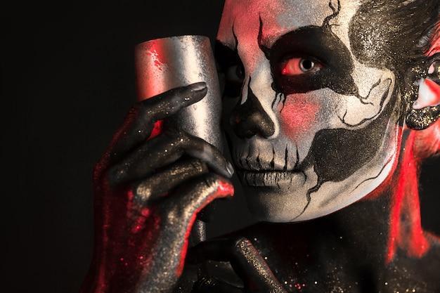 Jolie fille avec le maquillage squelette tient le verre