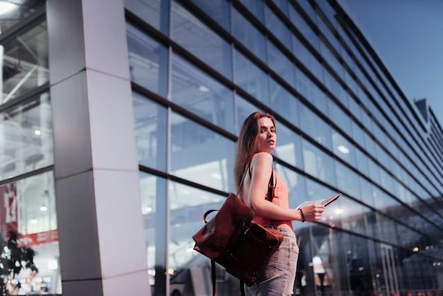 Jolie fille marchant près de l'aéroport et regardant la carte dans ses mains