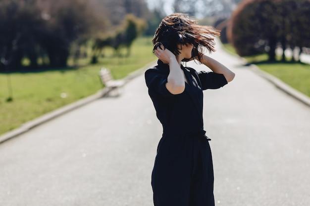 Jolie fille marchant sur la route du parc en journée ensoleillée