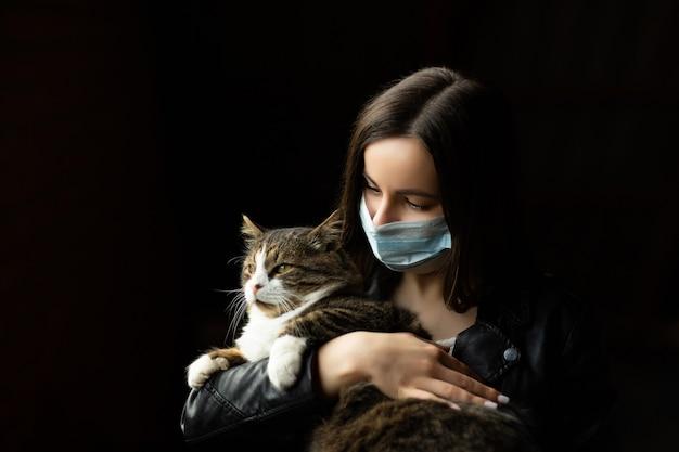 Jolie fille en masque médical tenant un chat sur un mur noir