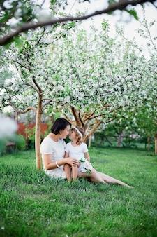 Jolie fille et mère assise et étreignant dans le jardin de printemps en fleurs femme heureuse et enfant, vêtue d'une robe blanche à l'extérieur, la saison du printemps arrive. concept de vacances fête des mères