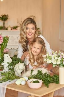 Jolie fille et mère jouant avec le lapin