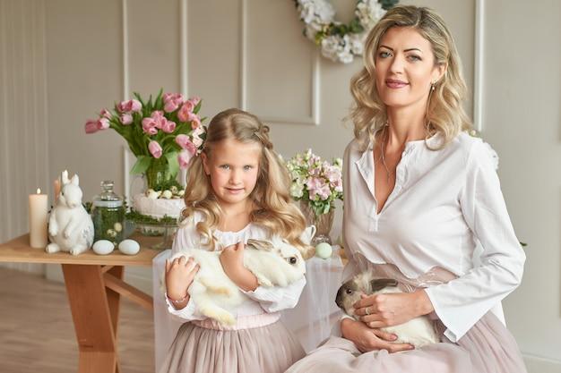 Jolie fille et mère jouant avec des lapins