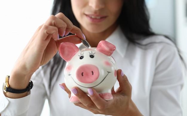 Jolie fille met une pièce de monnaie en céramique figurine de porc