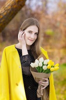 Jolie fille mignonne aux cheveux longs dans un manteau jaune et un bouquet de fleurs dans ses mains