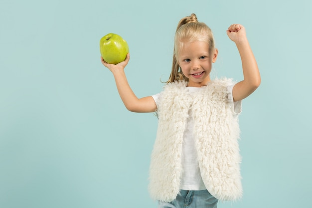 Jolie fille mignonne dans des vêtements légers cale des pommes