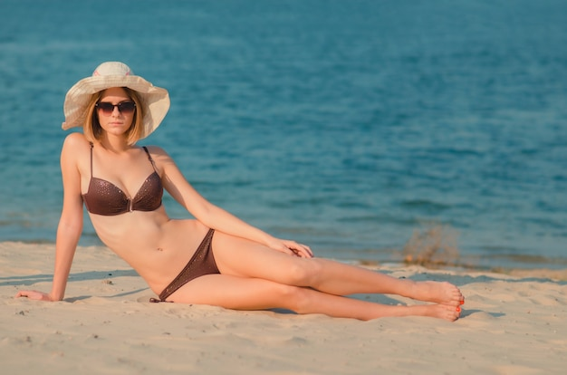 Jolie fille mince caucasienne dans des lunettes et un chapeau sur la plage, allongée sur du sable doré. loisirs et cocooning en bord de mer (océan, rivière, lac) en été et en journée ensoleillée.