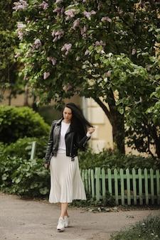 Jolie fille modèle en jupe midi d'été et veste en cuir posant près d'un arbre fleuri jeune femme brune en tenue de printemps posant à l'extérieur