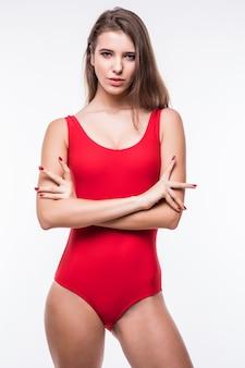 Jolie fille modèle en suite de natation tient les bras sur sa ceinture isolé sur fond blanc