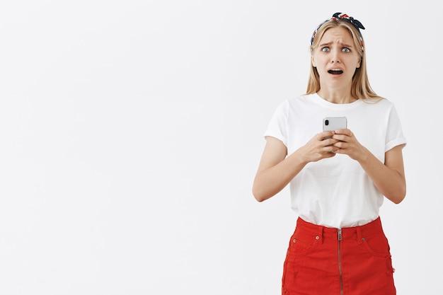 Jolie fille moderne à l'aide de téléphone portable et à la recherche anxieuse et inquiète