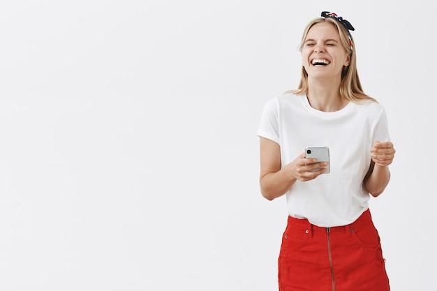 Jolie fille moderne à l'aide de téléphone portable et souriant