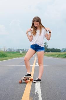 Jolie fille moderne jalonnant rue vide