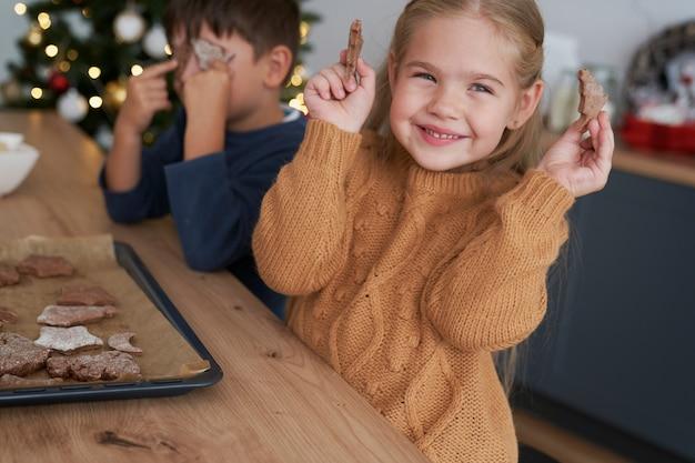 Jolie fille montrant des biscuits de pain d'épice faits maison