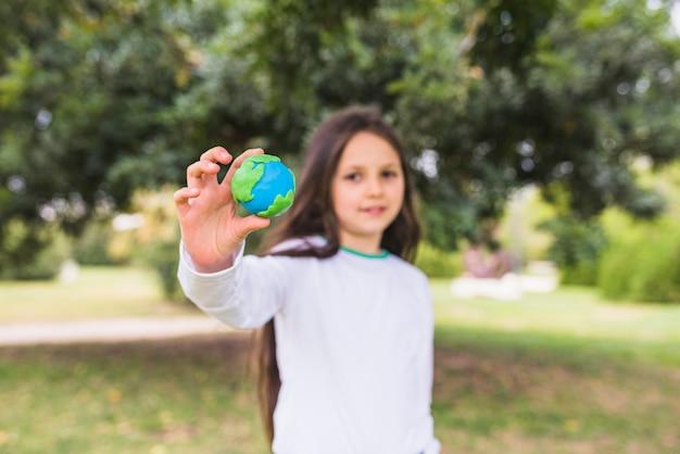 Jolie fille montrant un globe d'argile debout dans le parc