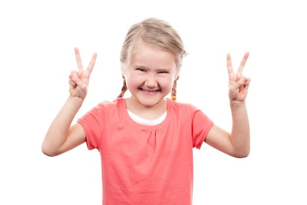 Jolie fille montrant le signe de la victoire sur l'espace blanc