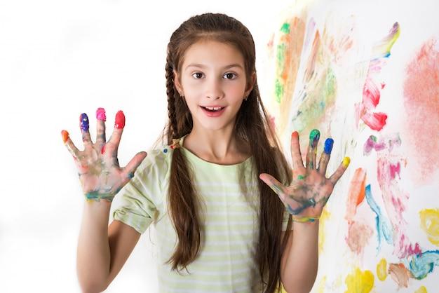 Jolie fille montre des mains tachées de peinture sur blanc