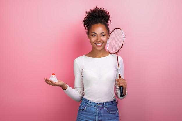 Jolie fille mulâtre debout avec des accessoires de badminton dans le studio en regardant la caméra