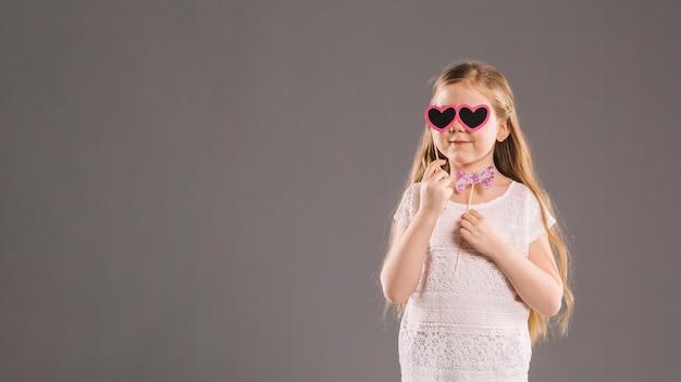Jolie fille avec un noeud papillon et des lunettes de coeur