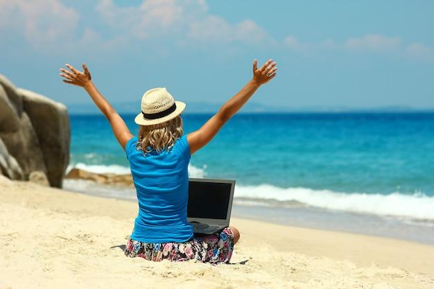 Jolie fille avec un ordinateur portable au bord de la mer