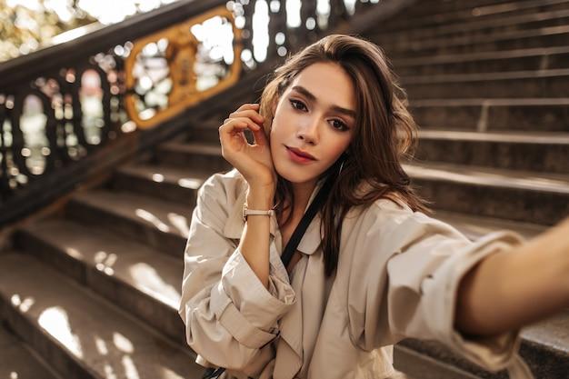 Jolie fille pâle avec un maquillage brillant et des cheveux noirs faisant un selfie en trench-coat beige et une belle pose à l'extérieur