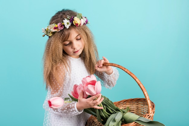 Jolie fille avec panier en regardant les fleurs de tulipes