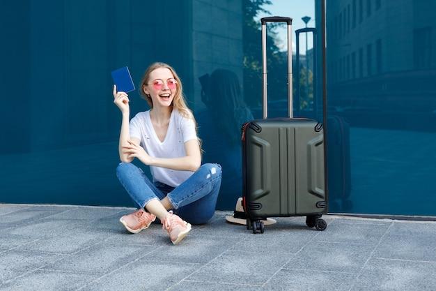 Jolie fille avec passeport et bagage à main est assise devant un bâtiment bleu en été