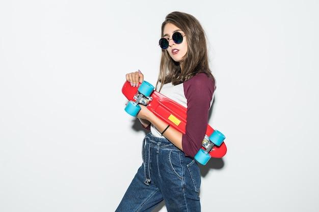 Jolie fille de patineur dans des vêtements décontractés et des lunettes de soleil noires tenant une planche à roulettes rouge isolée sur un mur blanc