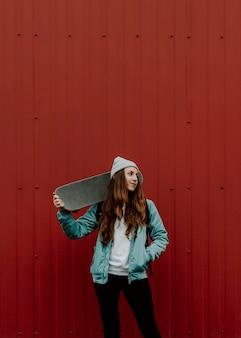 Jolie fille de patineur et sa planche à roulettes