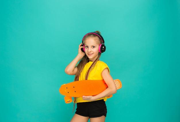 Jolie fille de patineur tenant la planche à roulettes