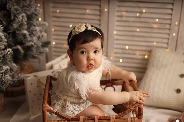 Jolie fille à la peau foncée assise dans un berceau en bois sur un fond avec des guirlandes