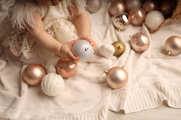 Une jolie fille à la peau foncée est assise sur une couverture tricotée blanche et joue avec des jouets d'arbre de noël