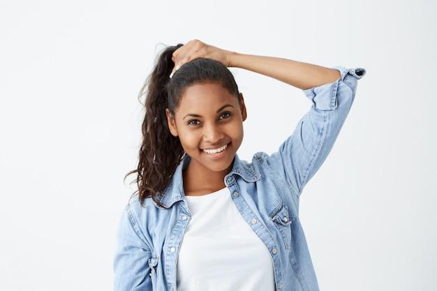 Jolie fille à la peau foncée souriante attachant joyeusement ses longs cheveux noirs ondulés en queue de cheval, se préparant avant de sortir avec des amis. jeune modèle féminin afro-américain posant