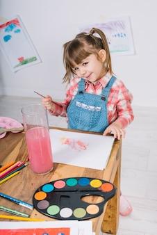 Jolie fille peignant à l'aquarelle sur papier