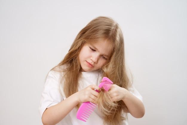 Jolie fille peigne les cheveux emmêlés sur un fond blanc. cosmétiques pour le soin des cheveux des enfants.