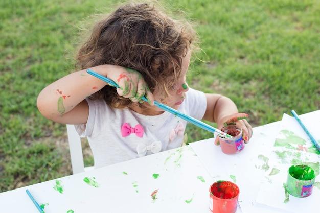 Jolie fille peinture au pinceau dans le parc