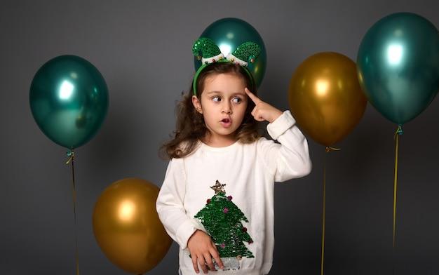 Une jolie fille pensive met son doigt sur sa tempe et regarde pensivement vers le bas, posant sur fond gris avec de beaux ballons à air métalliques dorés et verts brillants avec espace de copie pour l'annonce de noël